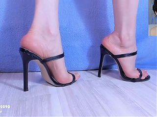 Cute feet in strappy black mules. Close up. 1080p.